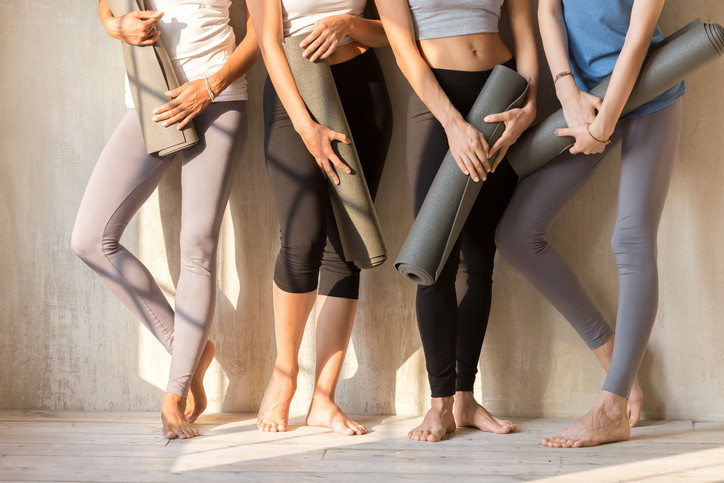 Group of sportive girls in a row with yoga mats